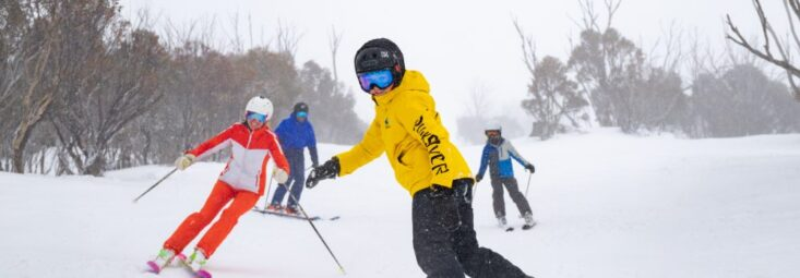 A group skiing and snowboarding at Thredbo Resort